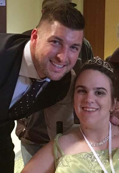 Tim Tebow posing with prom queen in wheelchair in green dress