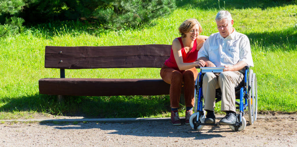 Man in a wheelchair with his wife in the park looking at a tablet